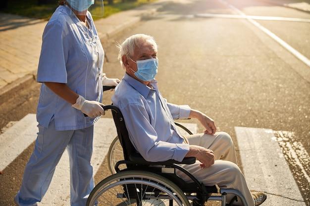 屋外で看護師と一緒に歩く薬マスクの老人