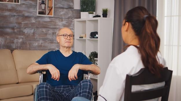 障害のある車椅子の老人と医療従事者。ナーシングホーム支援、ヘルスケア、医療サービスの医療従事者を持つ障害者高齢者