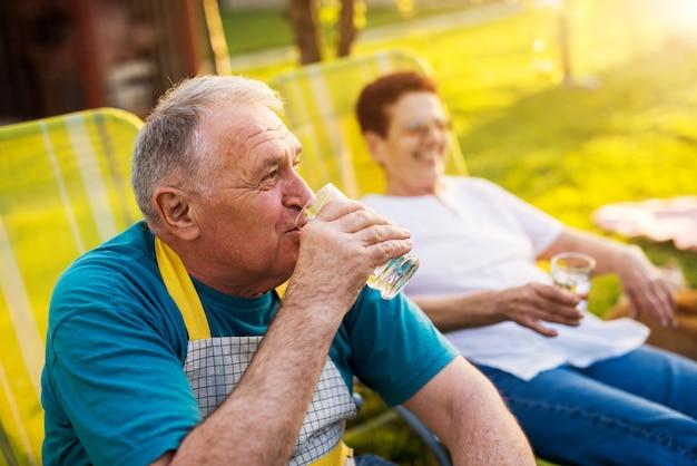 Пожилой мужчина пьет воду и смотрит вдаль, а его женщина сидит рядом с ним.
