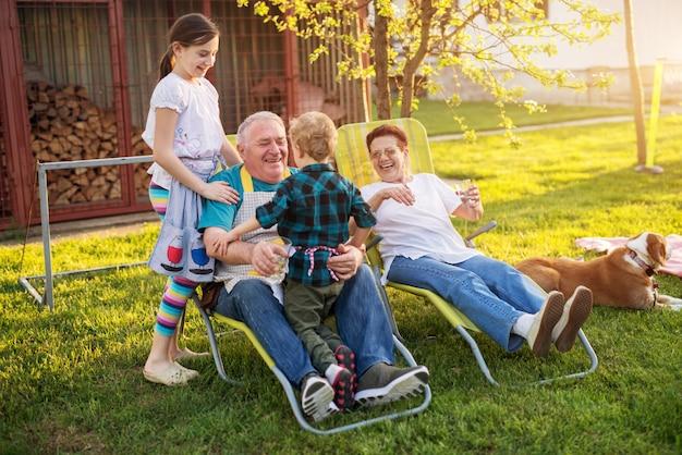 Пожилой мужчина держит своего маленького внука, в то время как его внучка стоит за ним, а его жена сидит рядом с ним в прекрасный день.