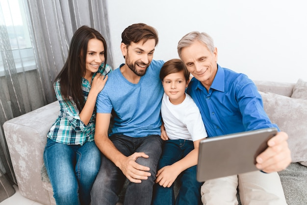 Elderly man is photographed on tablet with family at home.