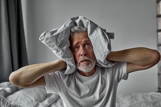 老人は、自宅で一人で、声を聞くのにうんざりしている、統合失調症、毛布で耳を閉じる