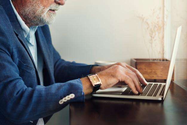 高齢者は、コンピュータのラップトップを使用しています