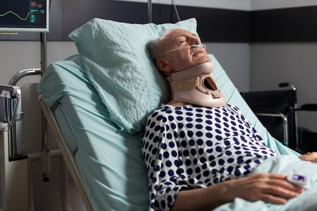 Elderly man laying in hospital room bed wearing cerival collar with iv drip oxygen mask helping pati...