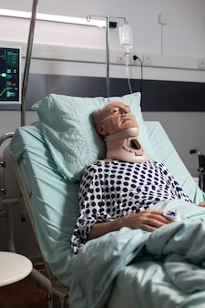 Elderly man laying in hospital room bed wearing cerival collar, with iv drip. oxygen mask helping patient breath in intensive care clinic. sleeping hospitalized man with neck trauma.