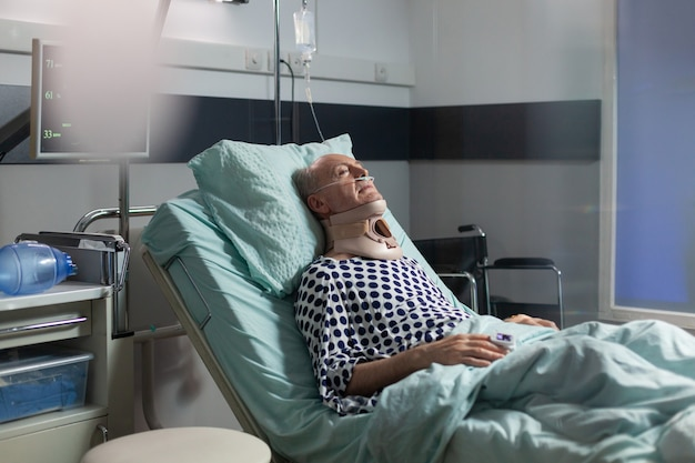 Elderly man laying in hospital room bed wearing cerival collar