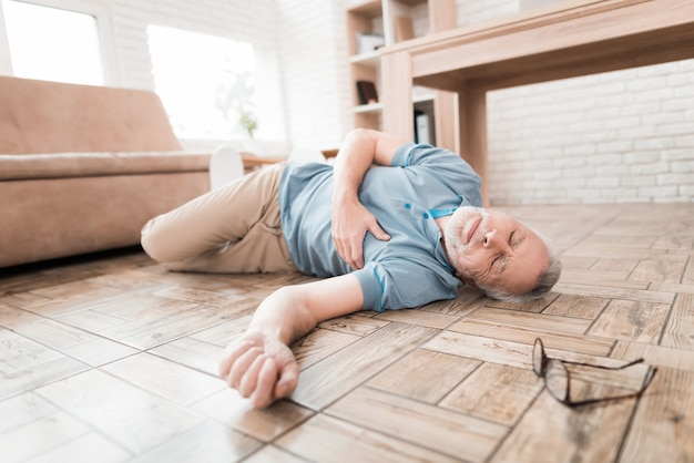 Elderly man lies on floor, clutching heart.