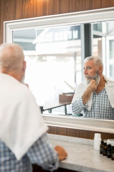 Elderly man looking at mirror in barber shop