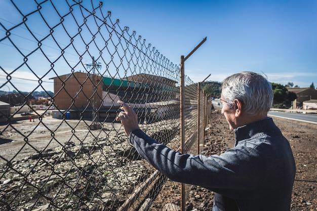 Elderly man looking through fence