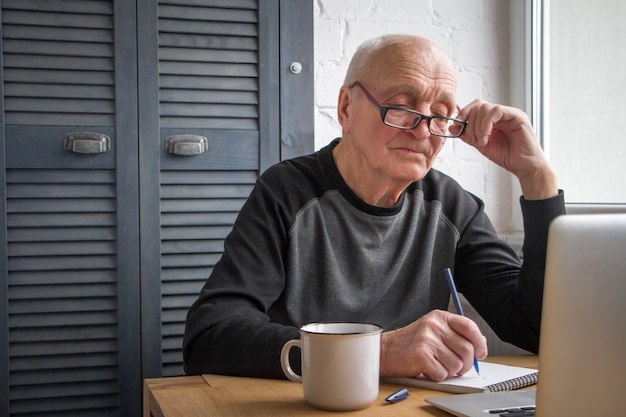 An elderly man looks at the laptop screen, makes notes in a notebook, writes taxes.