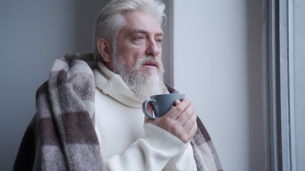 Пожилой мужчина смотрит в окно, пьет кофе дома, накрытый теплым одеялом