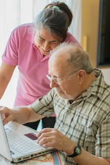 Elderly man looks and writes to the computer helped by his caregiver
