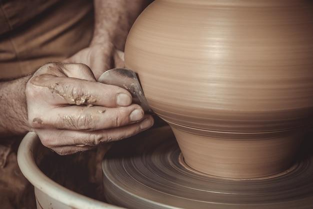 Elderly man making pot using pottery wheel in studio