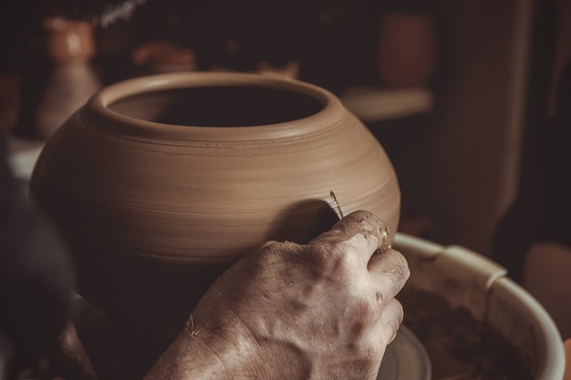 Elderly man making pot using pottery wheel