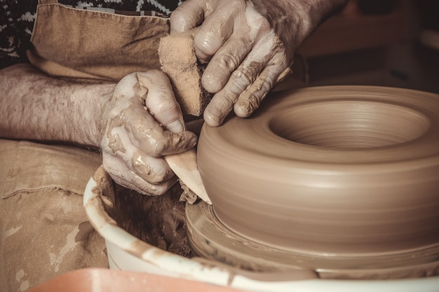 Elderly man making pot using pottery wheel