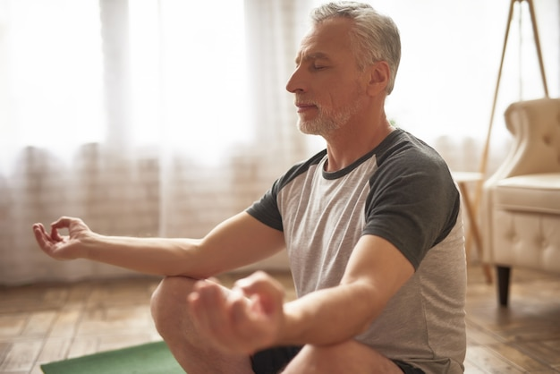 Elderly man meditating at home stress relief.