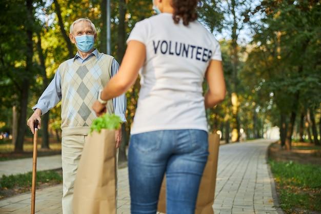 도시 공원에서 자원 봉사자를 만나는 노인