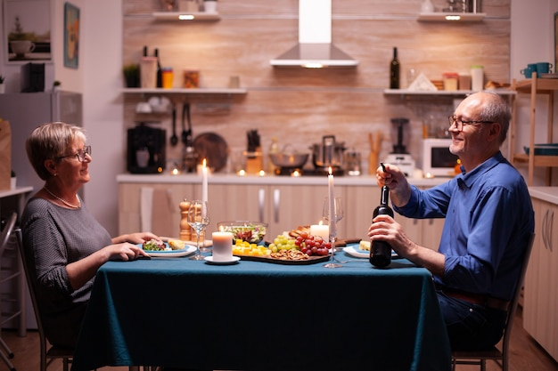 Elderly man opening a bottle of wine in kitchen during romantic dinner with wife . senior old couple talking, sitting at the table in dining room , enjoying the meal, celebrating their anniversary.