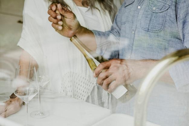 Elderly man opening a white wine bottle