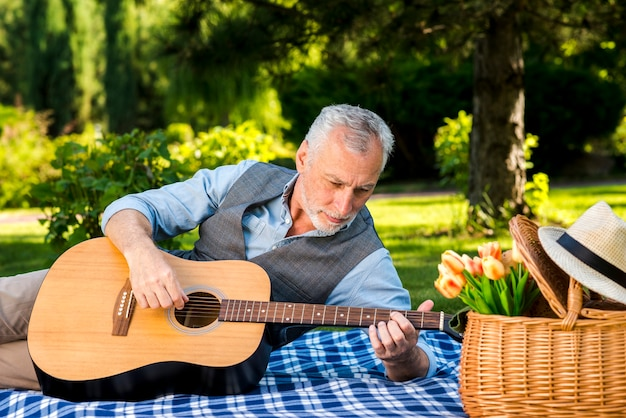 Elderly man playing guitar at the picnic