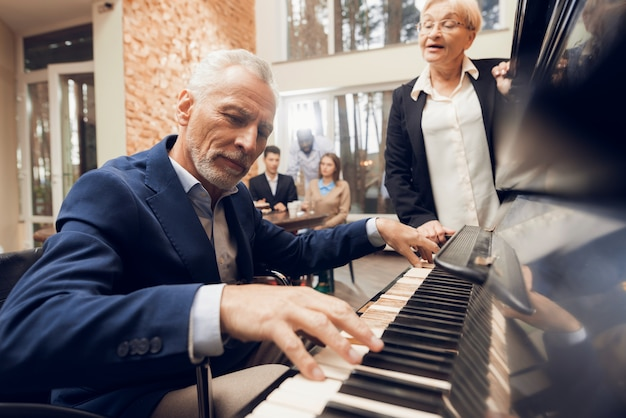 An elderly man plays the piano in a nursing home.