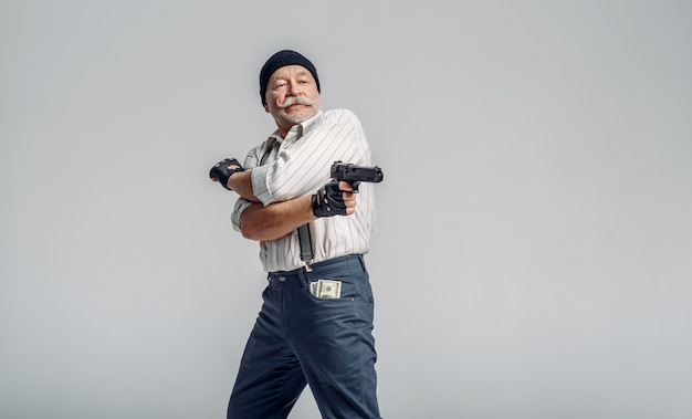 Elderly man poses with gun, gangster. mature senior in hat holds weapon, robber in old age
