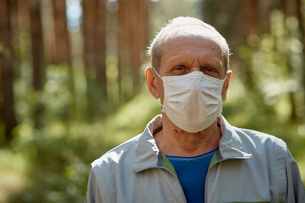An elderly man in a protective mask walks in the park, a walk in the fresh air after quarantine, a precautionary measure against the virus