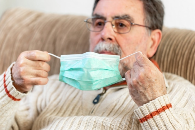 Elderly man putting a medical mask on his face to protect himself from coronavirus pandemic.