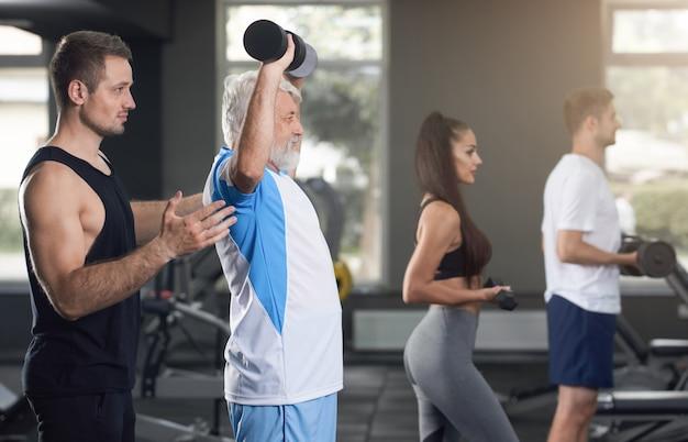 Elderly man raising dumbbells, trainer supporting.