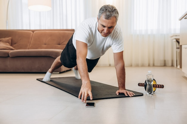 Elderly man reaches for phone to change music during excercise