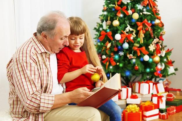 クリスマスの装飾が施されたリビングルームで孫娘と本を読んでいる老人