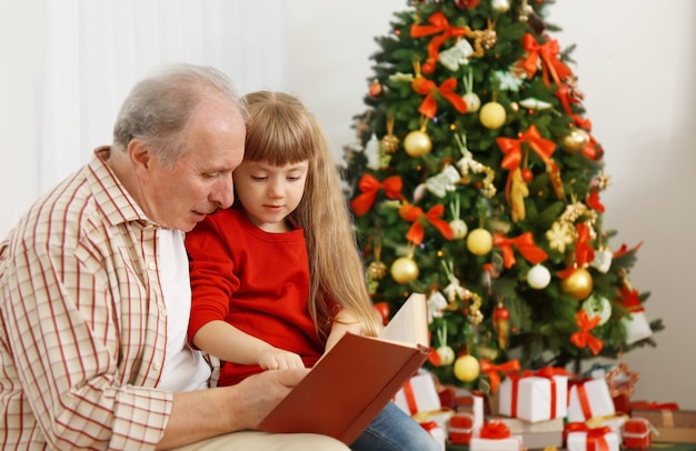Elderly man reading book with his granddaughter in living room decorated for christmas