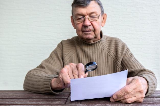 노인은 돋보기를 사용하여 종이에 작은 글씨를 읽습니다.