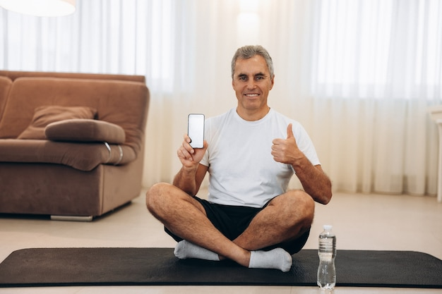 Elderly man really likes his favorite app for workout