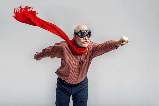 Elderly man in a red scarf and pilot glasses flying like a superman. cheerful mature senior