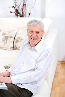 Elderly man relaxed, reading book  in living room