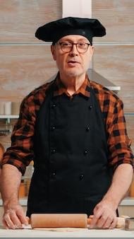Uomo anziano che rotola la pasta a casa davanti alla videocamera che spiega la ricetta passo dopo passo. influenzatore chef blogger in pensione che utilizza la tecnologia internet per comunicare sui social media con apparecchiature digitali