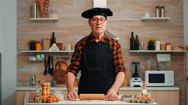 Elderly man rolling dough at home infront of video camera explaining recipe step by step. retired blogger chef influencer using internet technology communicating on social media with digital equipment