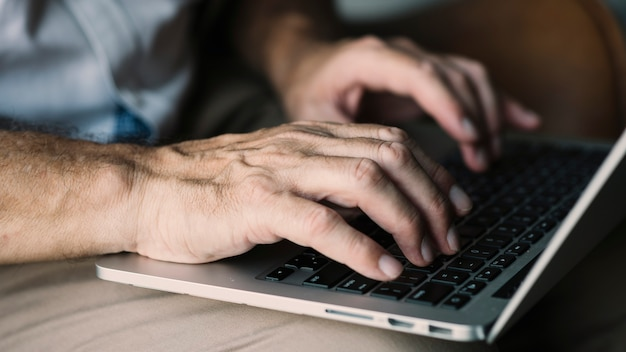 An elderly man's hand typing on laptop
