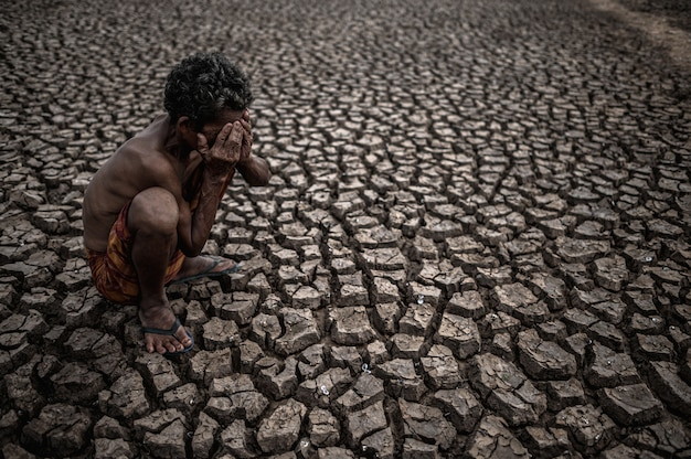 An elderly man sat bent his knees at dry ground and hands closed on his face, global warming