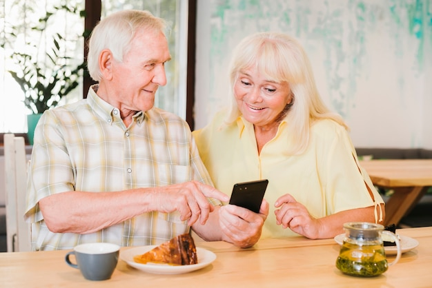 Elderly man showing smartphone to woman