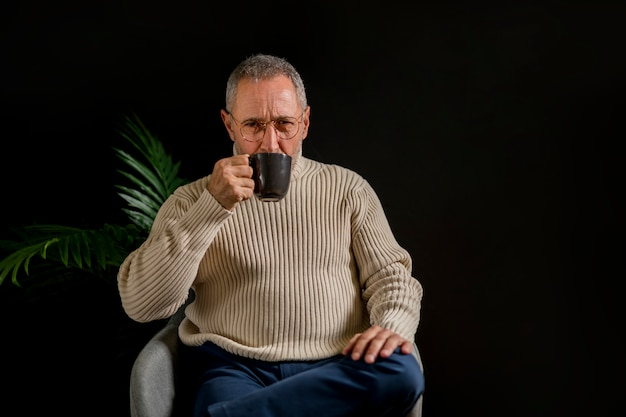 Elderly man sipping hot drink near plant