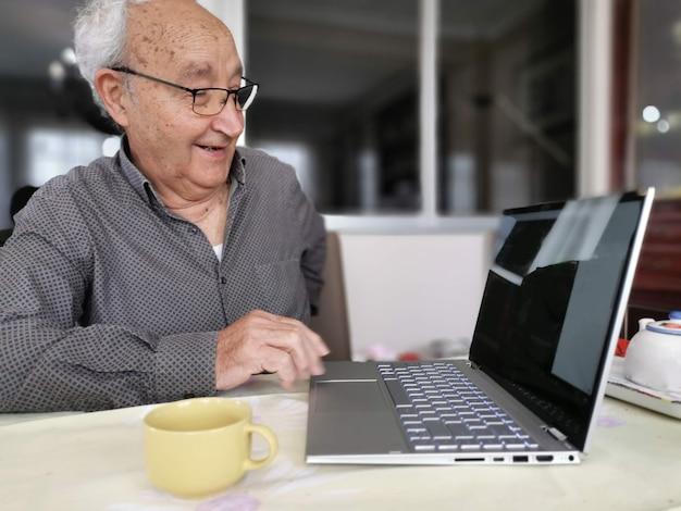 노인은 집에서 소파에 앉아 가족 친구들과 노트북으로 화상 통화를 하고, 노인 할아버지는 거실에서 소파에서 휴식을 취하며 온라인으로 웹캠 대화를 합니다.