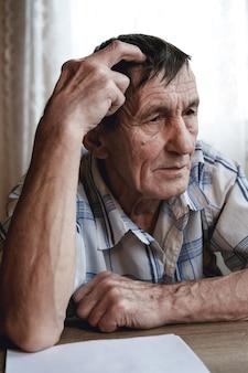 Пожилой мужчина сидит, держась за голову, страдает потерей памяти