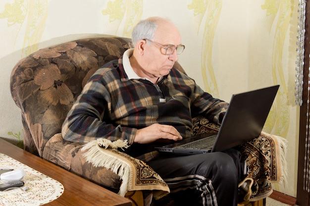 自宅の快適な肘掛け椅子に座って、ラップトップでインターネットをサーフィンしている彼の膝の上に彼のコンピューターを持っている老人