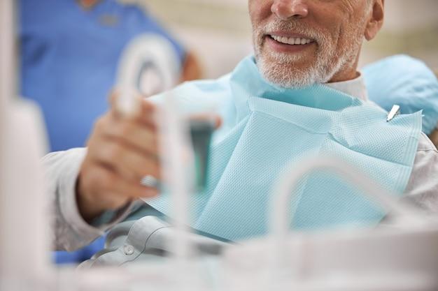 Пожилой мужчина сидит в стоматологическом кресле и держит чашку с жидкостью для полоскания рта