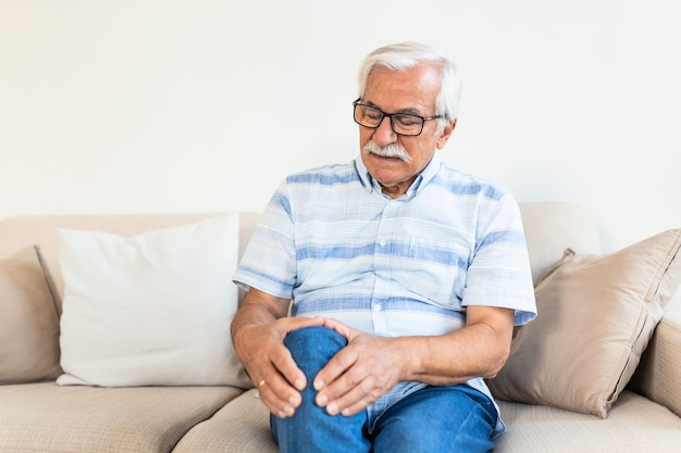 Пожилой мужчина сидит на диване у себя дома