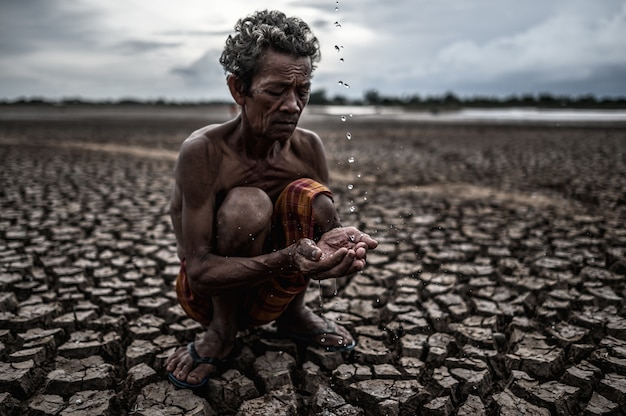 An elderly man sitting in touch with rain in the dry season, global warming, selection focus