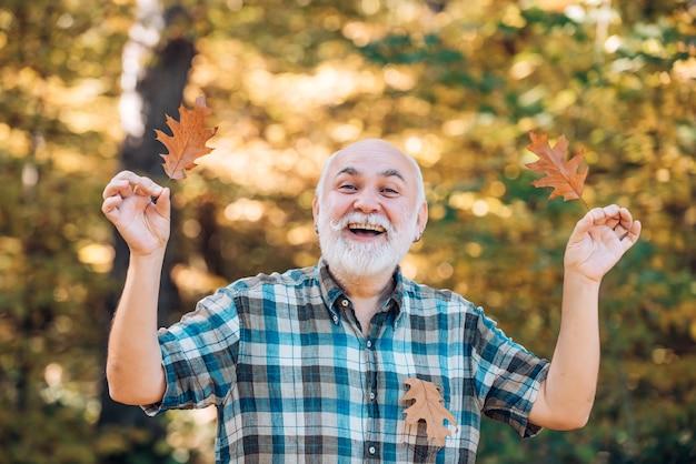 Пожилой мужчина улыбается на открытом воздухе на природе, дедушка отдыхает в осеннем парке, концепция выхода на пенсию ...