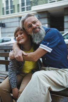그의 손자를 포옹하는 카메라에 웃 고 노인